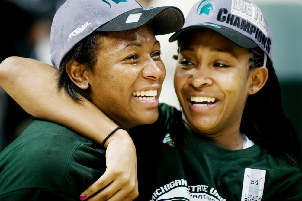 Senior forward Cetera Washington, right, hugs her teammate red-shirted junior Lykendra Johnson after raising the Big Ten Champion banner in Breslin Center on Thursday after the home game against Ohio State. Lauren Wood/The State News