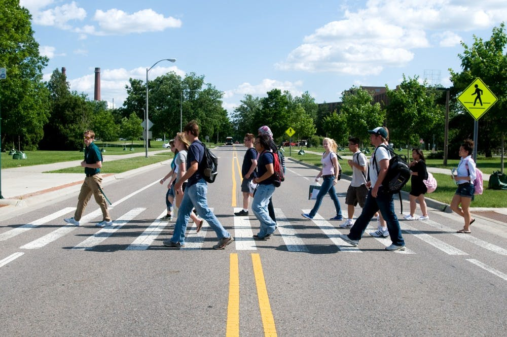 <p>Physiology junior Eric Bowden, far left, leads a group of incoming freshman on a walking tour of campus Monday on the first day of Academic Orientation Program.</p>