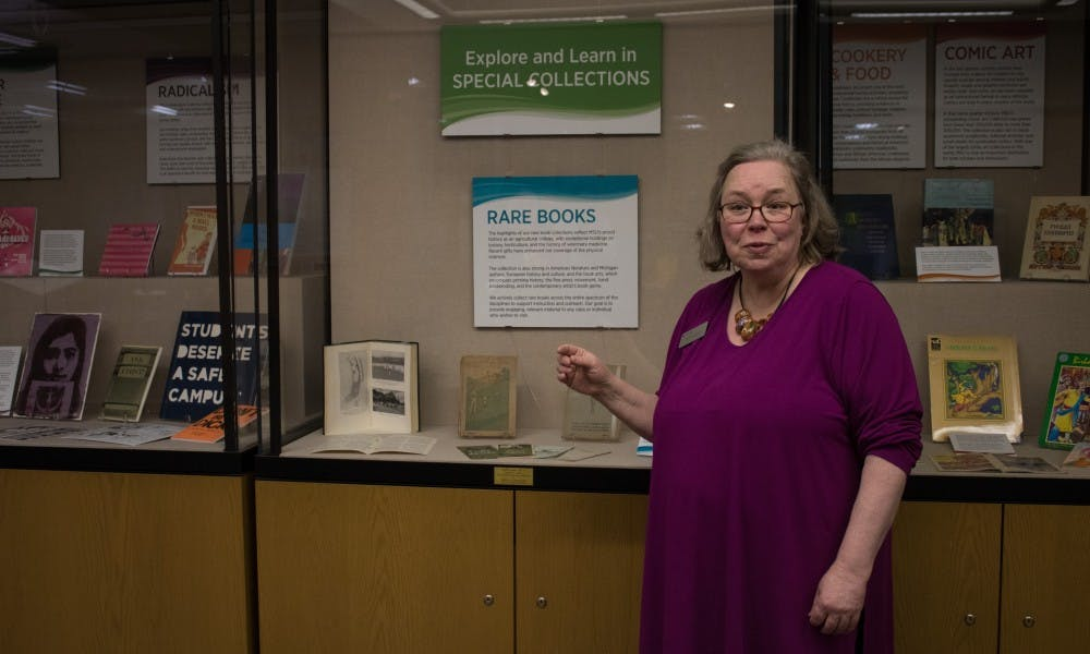 Ruth Ann Jones, the special collections education and outreach librarian, stands next to a display of rare books at the Main Library on Jan. 11, 2019. Jones curates and changes this display every few months to fit themes of popular culture, cook books and comic art.