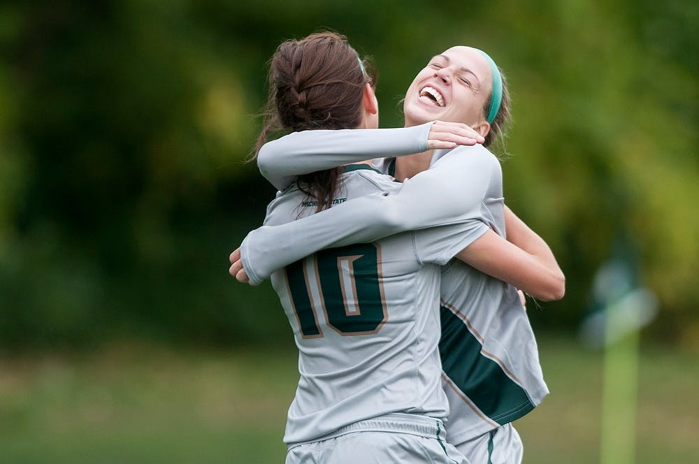<p>Senior midfielder Megan Marsack, 10, hugs freshman forward Jamie Cheslik after Marsack's goal during the game against Nebraska on Oct. 5, 2014, at DeMartin Soccer Stadium at Old College Field. The Spartans defeated the Cornhuskers, 3-1. Jessalyn Tamez/The State News</p>