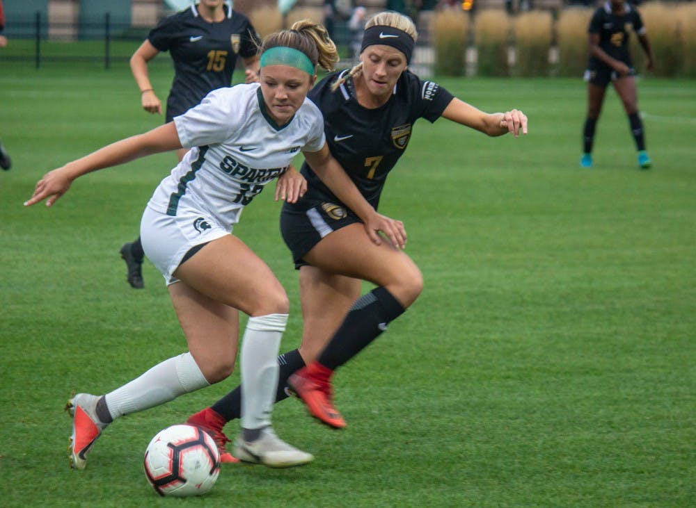 <p>Defender Athena Biondi (13) runs with Oakland's midfielder Ali Amante (7) during the game against Oakland on Sept. 6, 2018 at DeMartin Stadium. The Spartans defeated the Grizzlies, 2-0.</p>