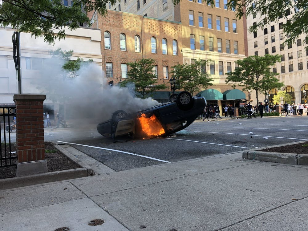 A car was set on fire during a protest in Lansing, Michigan. Prior, the owner of the vehicle was taken into custody after driving through a crowd of people.