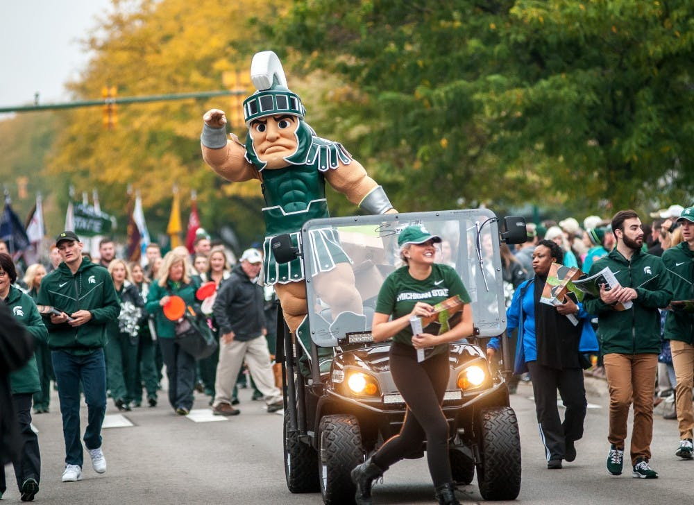 <p>Sparty rides along during the MSU Homecoming Parade on Oct. 5, 2018 along Grand River Avenue.</p>