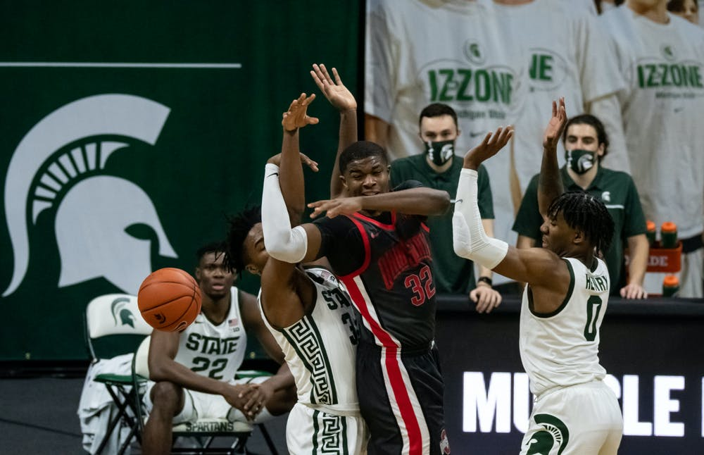 <p>Players wrestle for the ball during the MSU men&#x27;s basketball game against OSU at the Breslin Center on Feb. 25, 2021.</p>