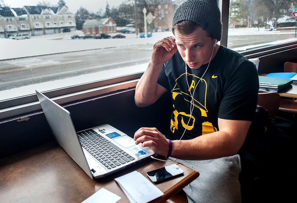 """<p>Psychology junior Cody Thomas adjusts his headphones before studying at Biggby Coffee, 270 W. Grand River Ave., March 19, 2013. Thomas was diagnosed with attention deficit hyperactivity disorder, or <span class=""""caps"""">ADHD</span>. Justin Wan/The State News</p>"""