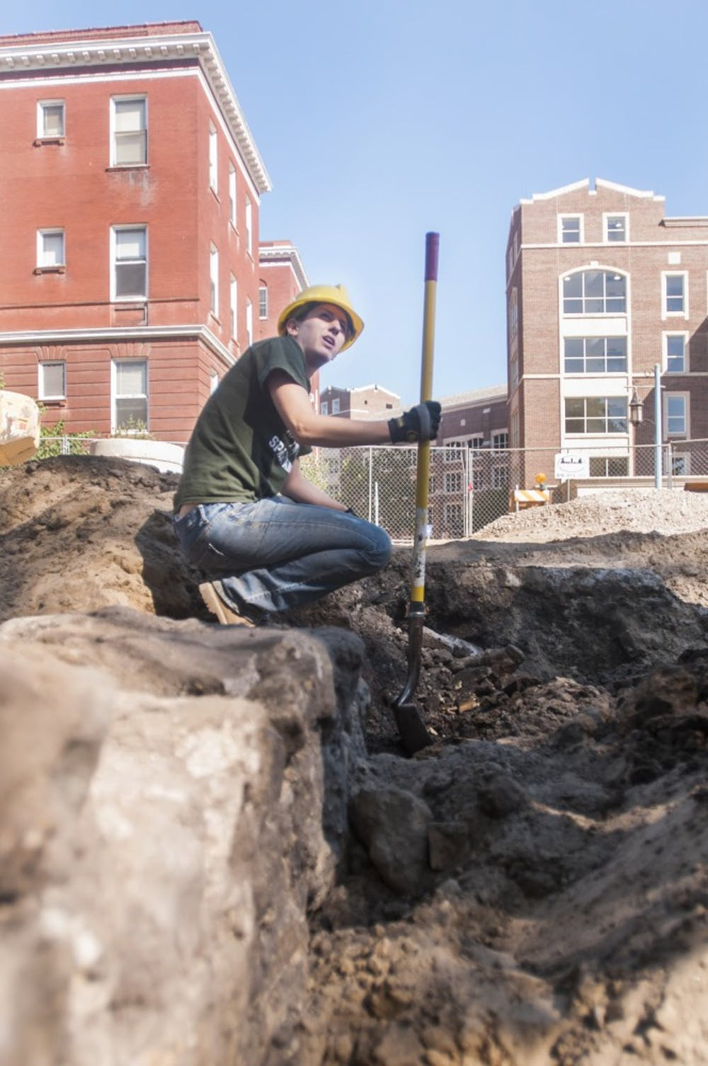 Katy Meyers, campus archeologist and graduate student digs at the site of the foundation of an old boiler room Tuesday, July 10, 2012 behind Morrill Hall.  Construction workers came across the structure last week while working on campus. Adam Toolin/The State News
