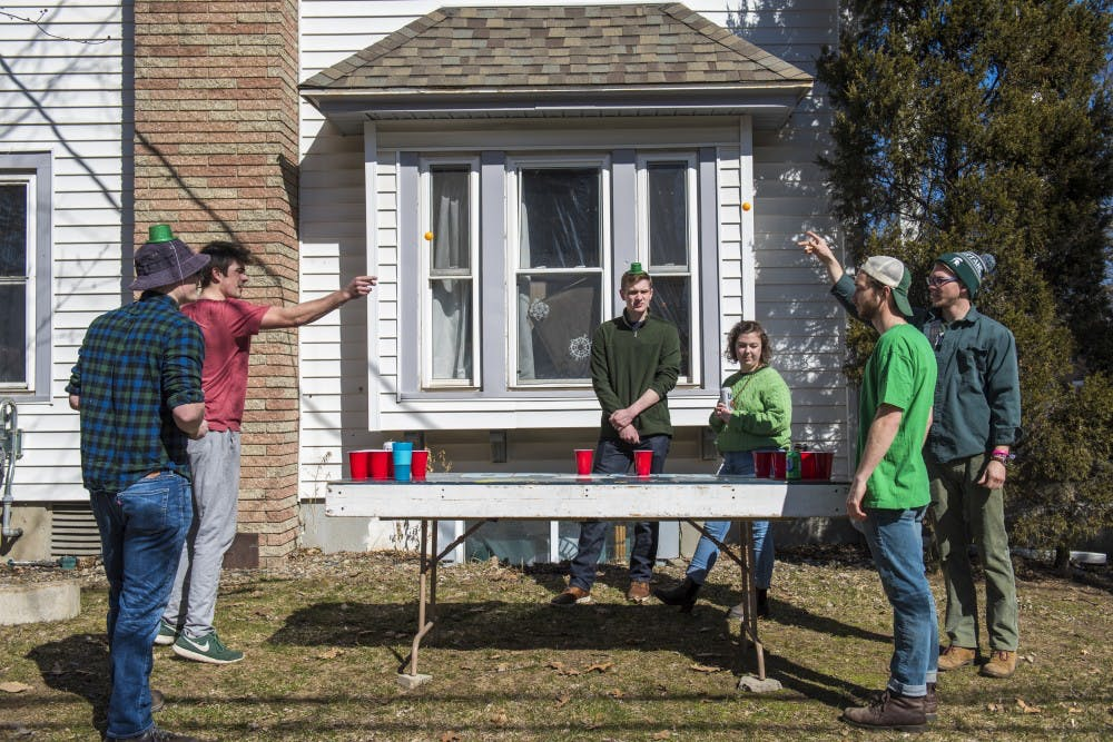<p>Kinesiology junior Kevin Stelmach, left, and kinesiology senior Ian Koskinen, right, throw ping pong balls during St. Patrick's Day on March 17, 2018 at Orion House along M.A.C. Avenue.</p>