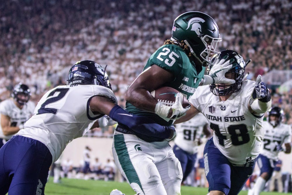 Junior wide receiver Darrell Stewart (25) stiff arms a defender during the game against Utah State on Aug. 31 at Spartan Stadium. The Spartans defeated the Aggies, 38-31.