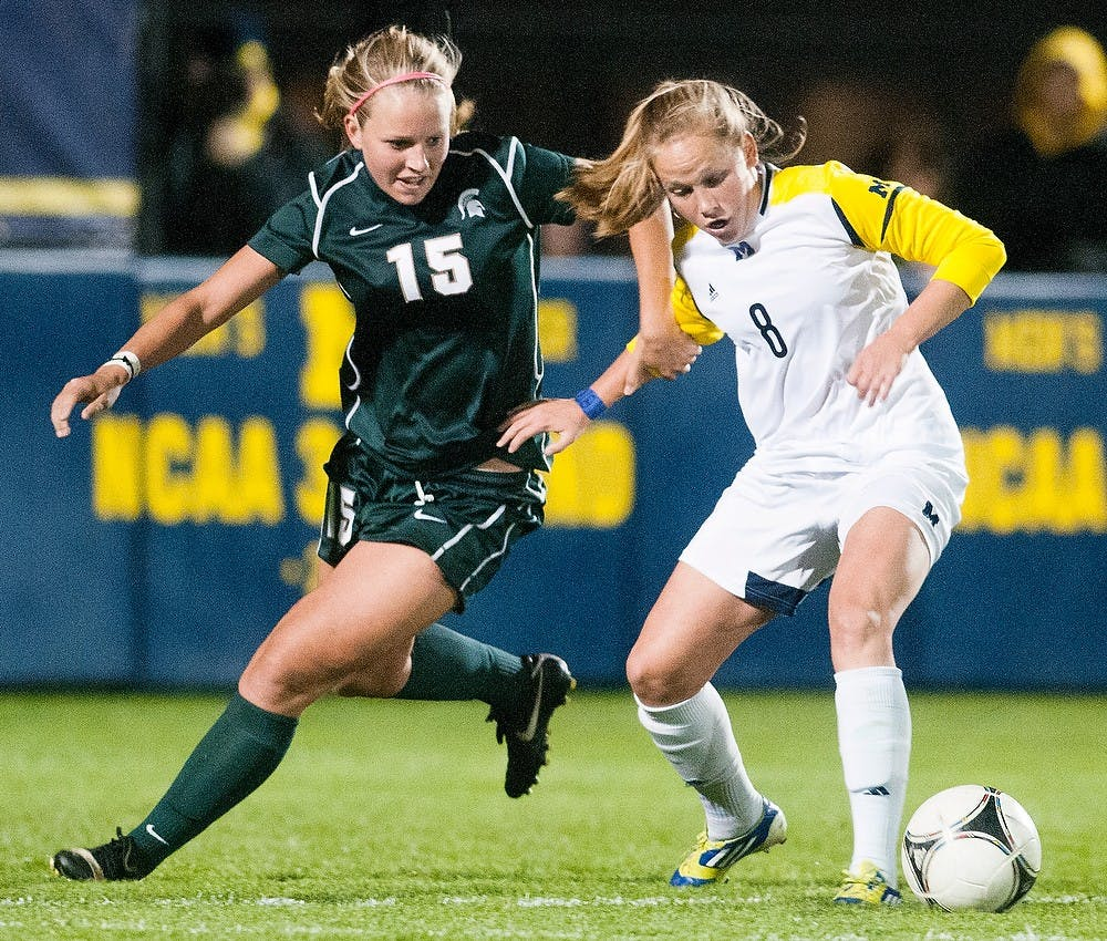 <p>Junior defender Kelsey Mullen tries to steal the ball away from Wolverine midfielder Tori McCombs on Wednesday, Oct. 10, 2012 at the U-M Soccer Stadium in Ann Arbor. The Spartans gained momentum in the first half after scoring a goal, but could not overcome the Wolverines in the end, losing 2-1 in overtime. Julia Nagy/The State News</p>