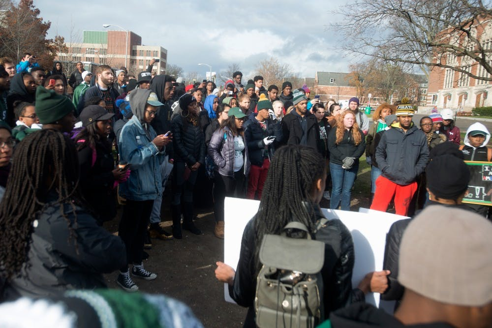 <p>Students gather around the rock after a march on Nov. 13, 2015, at the rock on Farm Lane. A police escort followed the march, where students held signs and yelled chants in solidarity with the students at the University of Missouri. </p>