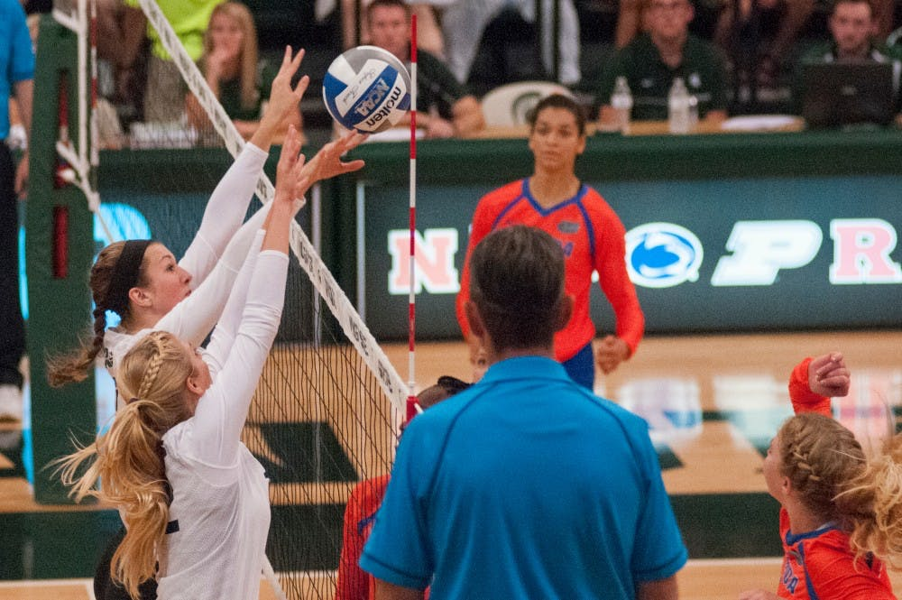 Junior middle blocker Alyssa Garvelink (17) and junior setter Rachel Minarick (12) block the volleyball from going over the net during the volleyball game against the University of Florida on Sept. 4, 2016 at Jenison Field House. The Spartans were defeated by the Gators, 3-0.