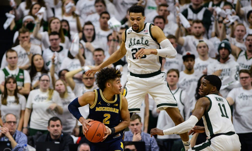 Senior forward Kenny Goins (25) jumps over Michigan forward Jordan Poole (2) during the first half of the game against Michigan at Breslin Center, March 9, 2019.