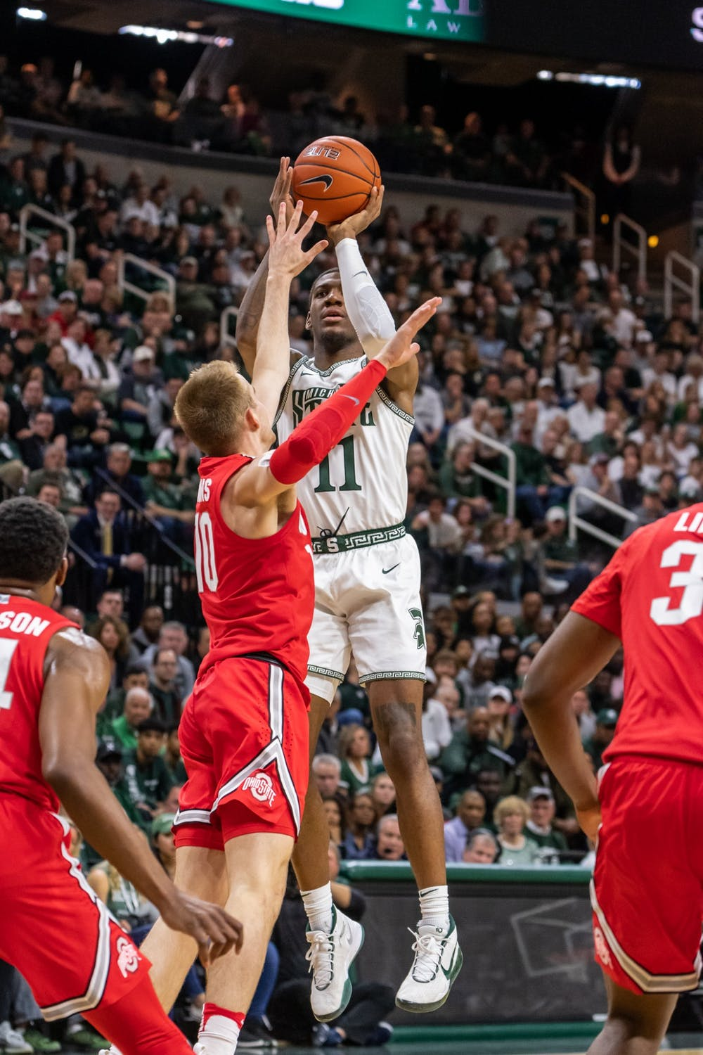 Sophomore forward Aaron Henry (11) shoots over Ohio State's Justin Ahrens (10). The Spartans defeated the Buckeyes, 80-69, at the Breslin Student Events Center on March 8, 2020.