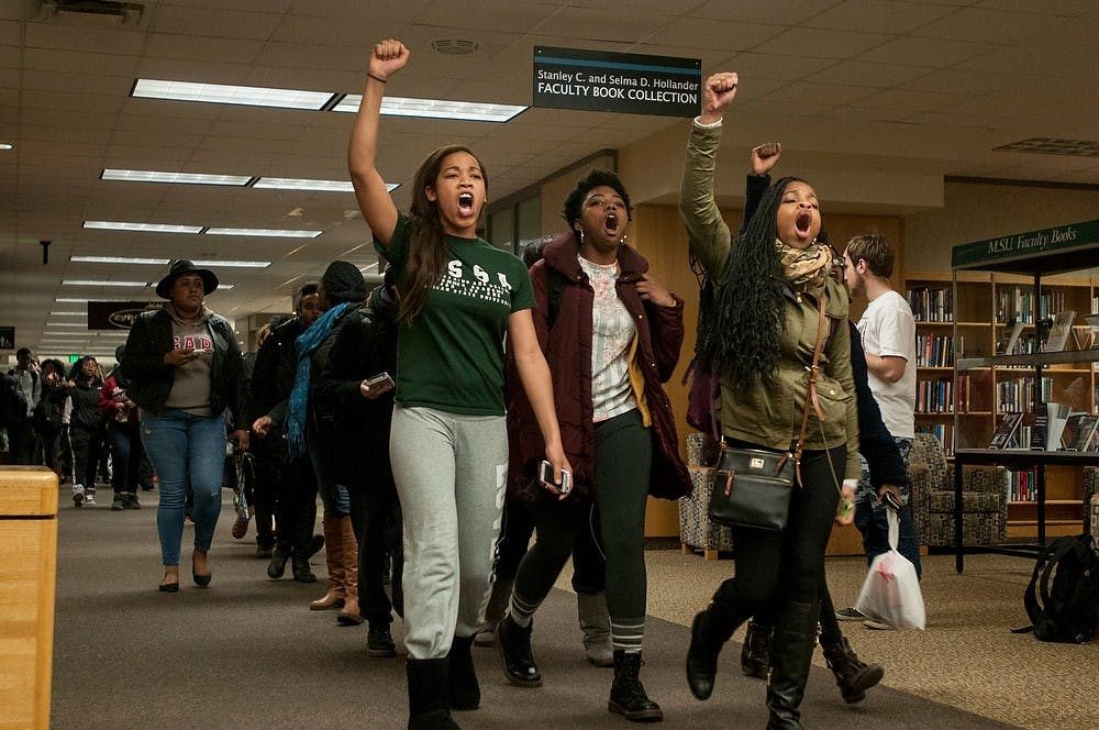 "<p>Lyman Briggs and human biology senior Chantelle Washington, left, leads the march with other protesters Dec. 7, 2014, during a die-in protest at the MSU Library. ""It is sad that we have to be lying dead in the streets to be relevant,"" Washington said. The group of students blocked the entrances and walk ways in the library and marched afterwards in protest of police violence against black people while other MSU students were present to study for finals week. Raymond Williams/The State News</p>"