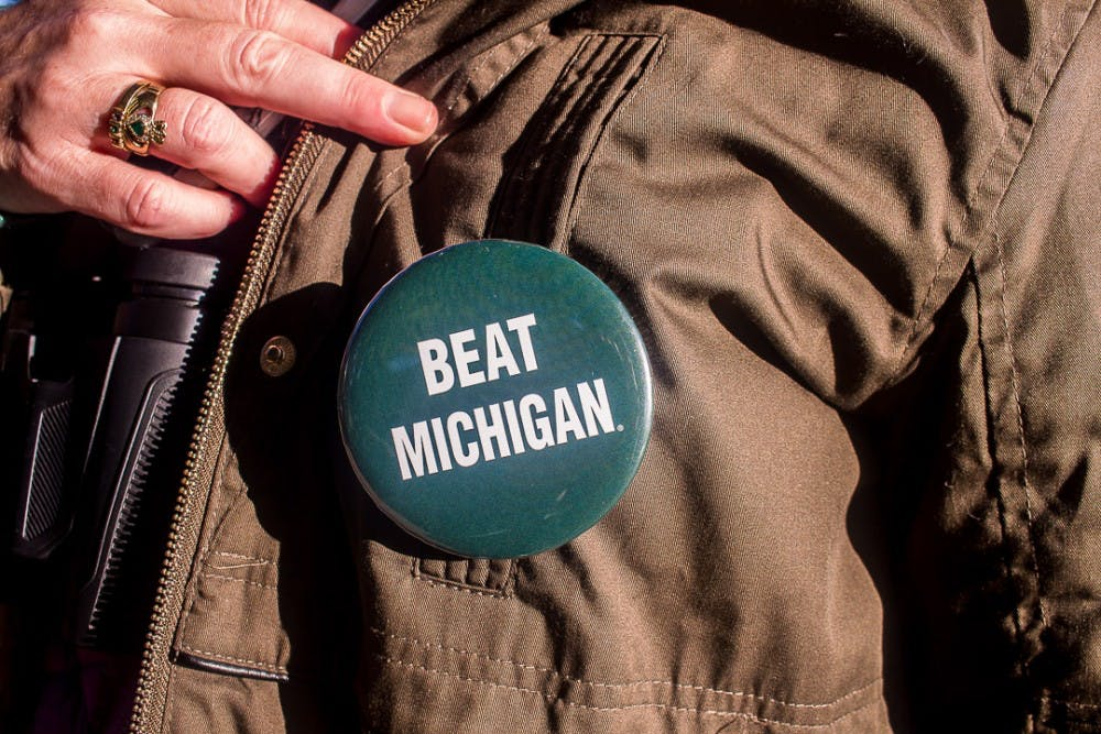 A Spartan fan shows off her pin before the game against Michigan on Oct. 20, 2018 at Spartan Stadium.