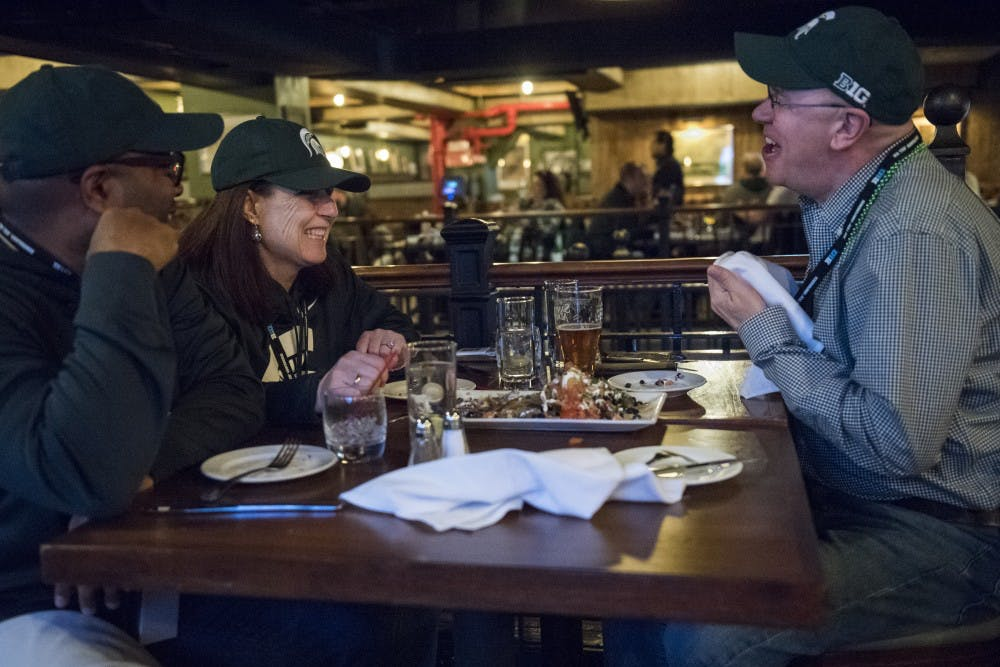 From left, Worcester, Mass. resident Calvin Hill, Worcester, Mass. resident and MSU alumna Susan Scully-Hill and Glen Ellyn, Ill. resident and MSU alumnus Dennis Jarrard laugh together before the Big Ten Men's Basketball semifinal game between Michigan State and Michigan on March 3, 2018 at Mustang Harry's in New York. Between one and two hundred MSU fans and alumni gathered at Mustang Harry's before the game. (Nic Antaya | The State News)