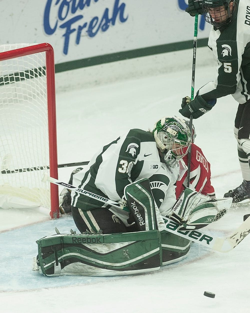 <p>Junior goaltender Jake Hildebrand blocks an Ohio State attempt Jan. 23, 2015, during a game against Ohio State  at Munn Ice Arena. The Spartans defeated the Buckeyes, 4-1. Alice Kole/The State News</p>