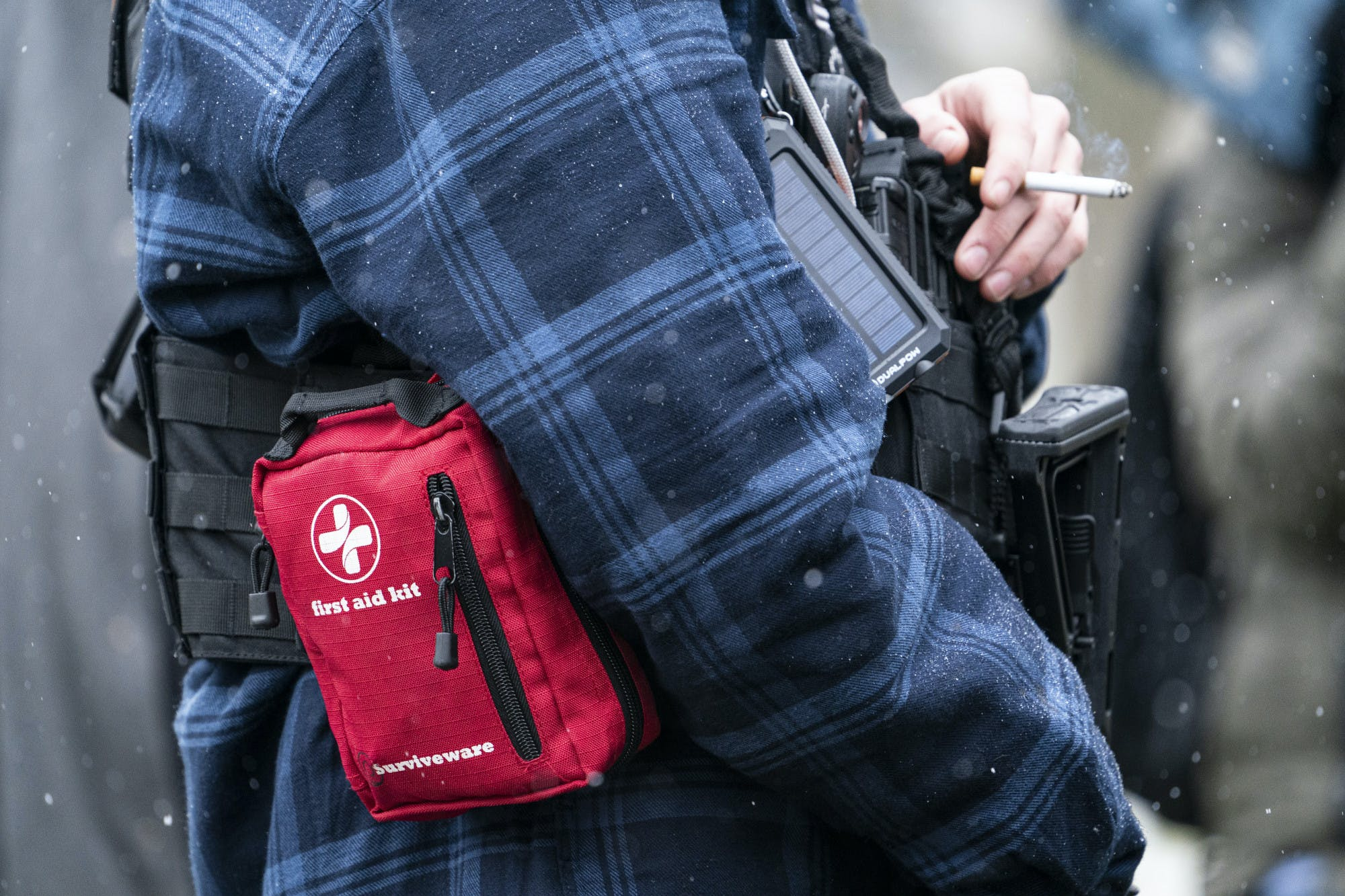 A person armed with a gun and first aid kit smokes a cigarette.