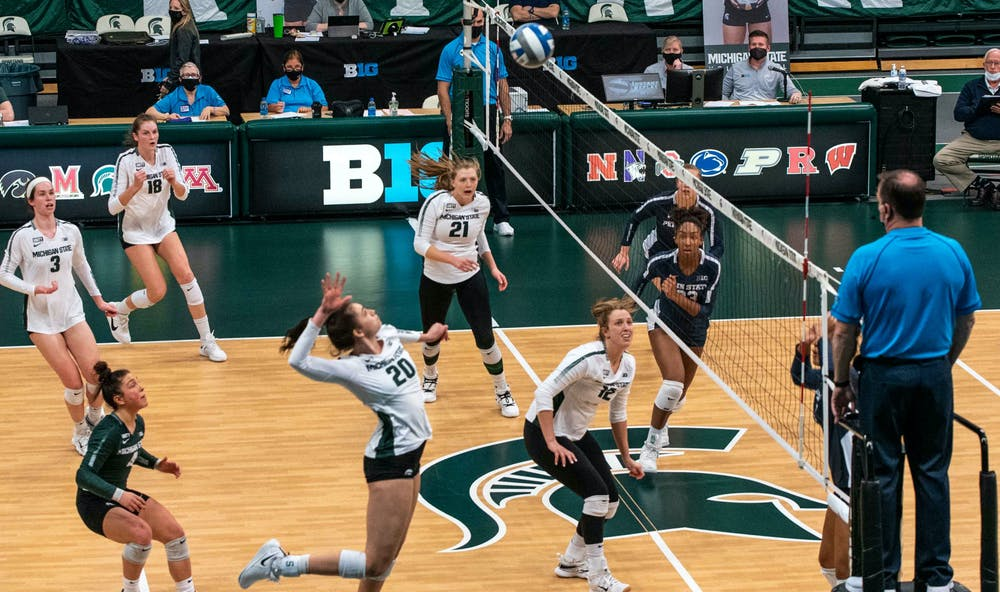 <p>Sophomore outside hitter Cecilee Max-Brown (20) jumps to kill the ball as the rest of the stadium watches. The Nittany Lions shut out the Spartans, 3-0, on March 20, 2021. </p>