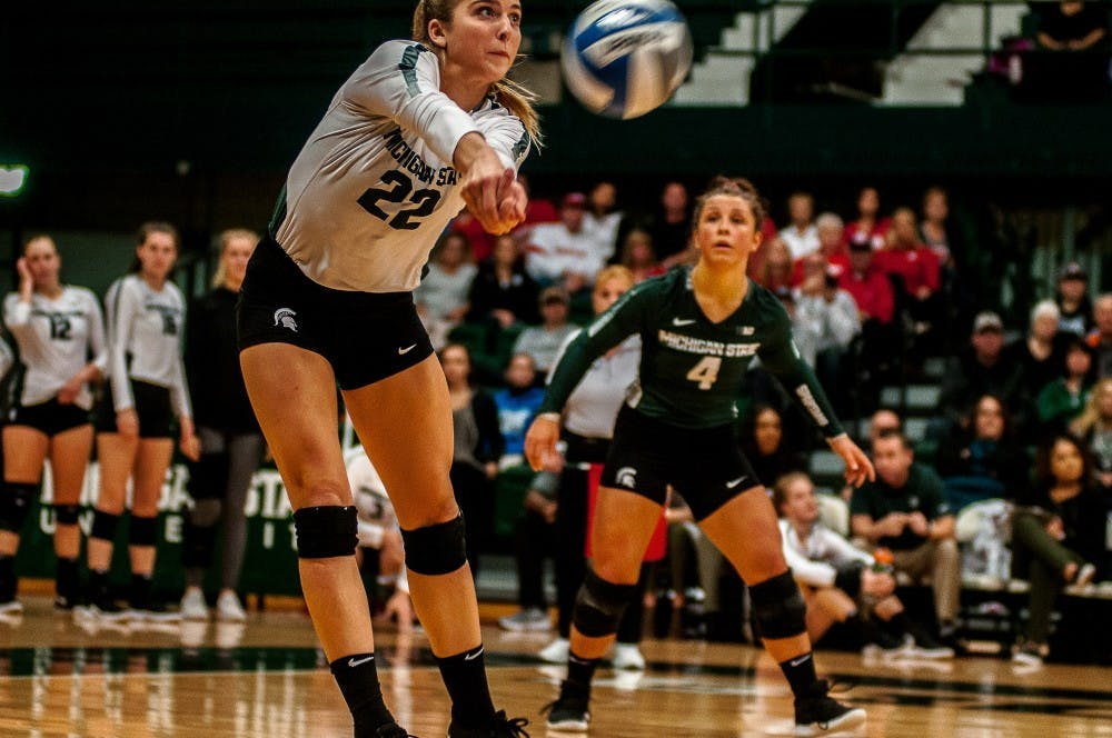 Junior defense Samantha McLean (22) hits the ball during the game against Wisconsin on Oct. 27, 2018 at Jenison Fieldhouse. The Badgers beat the Spartans, 3-0.