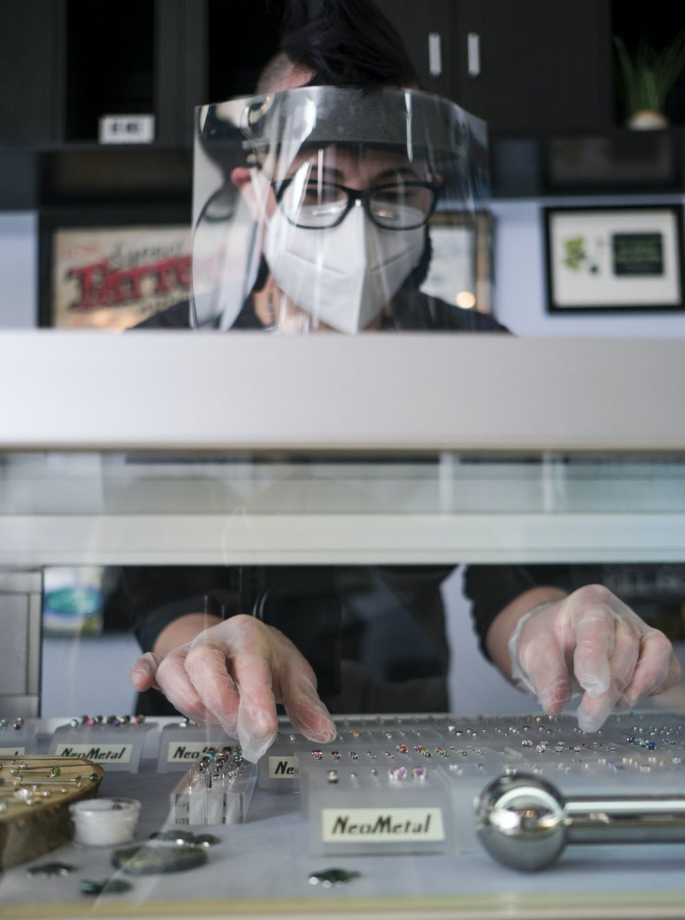 <p>Renee McKeith, a piercer at Splash of Color in East Lansing organizing the jewelry on display on March 13, 2021.</p>