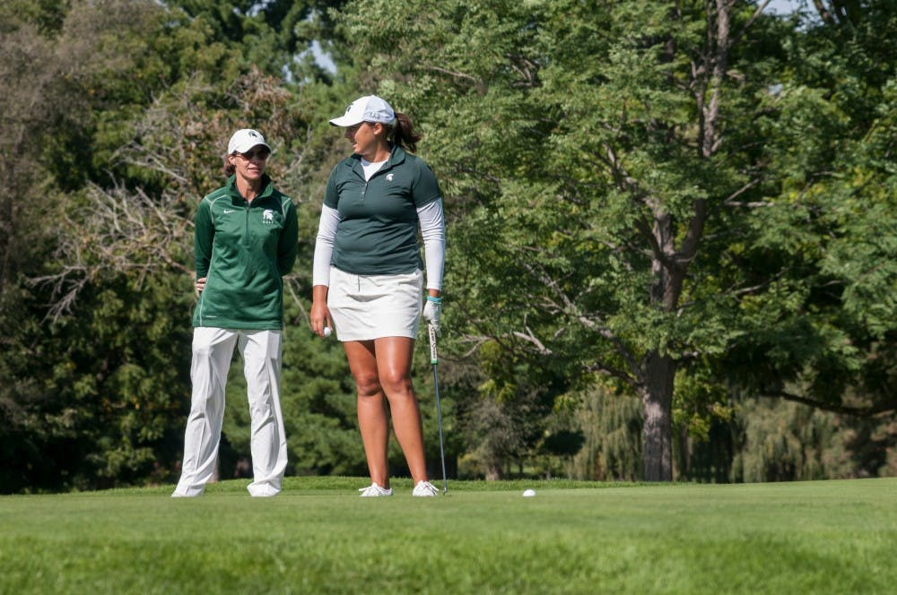 Women's golf head coach Stacy Slobodnik, left, talks with redshirt-junior Katie Sharp before a putt on Sept. 25, 2016 at Forest Akers West Golf Course. Slobodnik has held the head coaching position at MSU for 19 years.