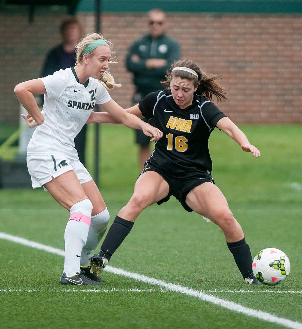 <p>Senior forward Paige Wester fights for the ball against  Iowa midfielder Anne Thomas during the game against the University of Iowa on Oct. 2, 2014, at DeMartin Soccer Stadium at Old College Field. The Spartans lost to the Hawkeyes 0-1. Raymond Williams/The State News</p>
