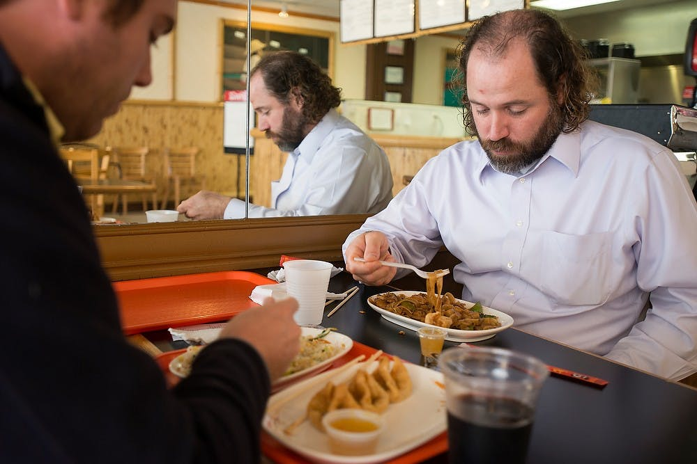 <p>Laingsburg, Mich., resident Aaron Wekenmen, right, and Williamston, Mich., resident Mike Mitchell eat lunch Sept. 18, 2014, at Thai 102 Degrees, 225 M.A.C. Ave., in East Lansing. Julia Nagy/The State News</p>