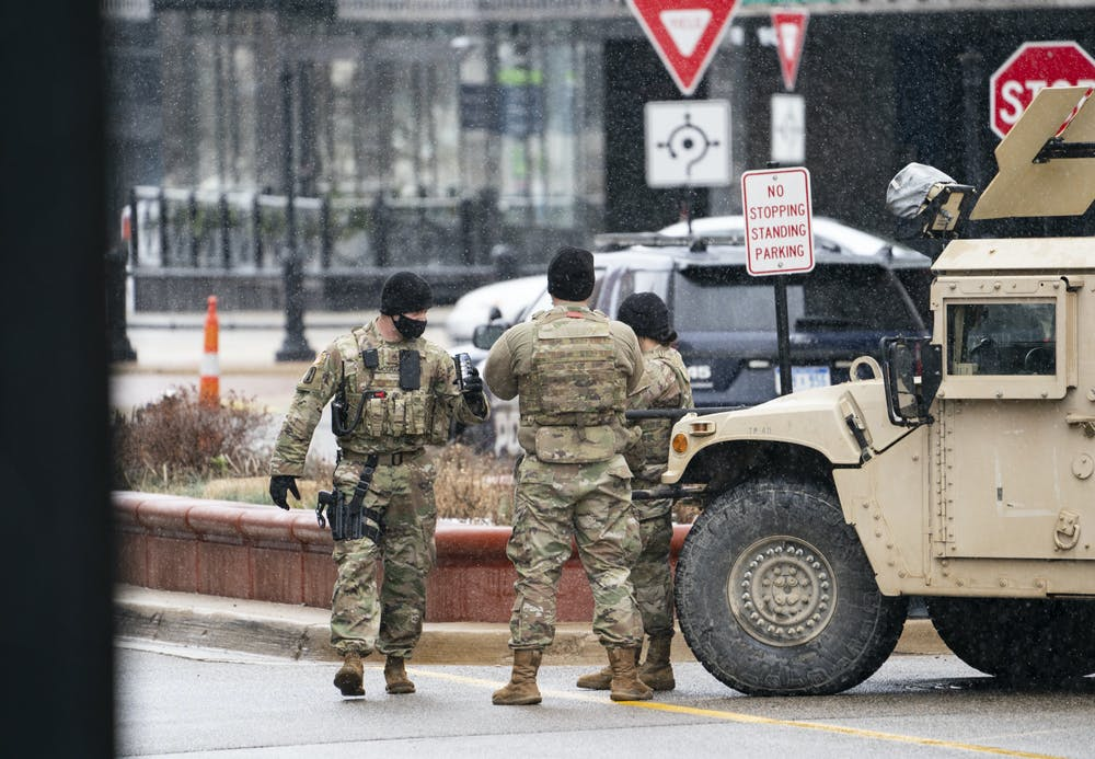 <p>National Guard members stand beside a Humvee 