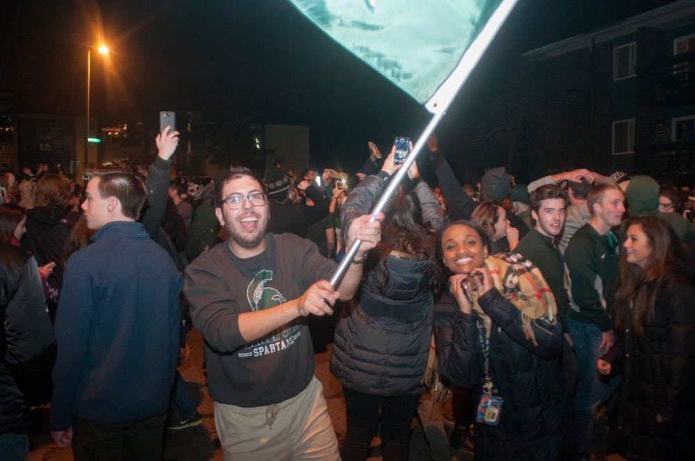 Students wave a MSU flag to celebrate after MSU's victory over Iowa on Dec. 5th, 2015, at Cedar Street.