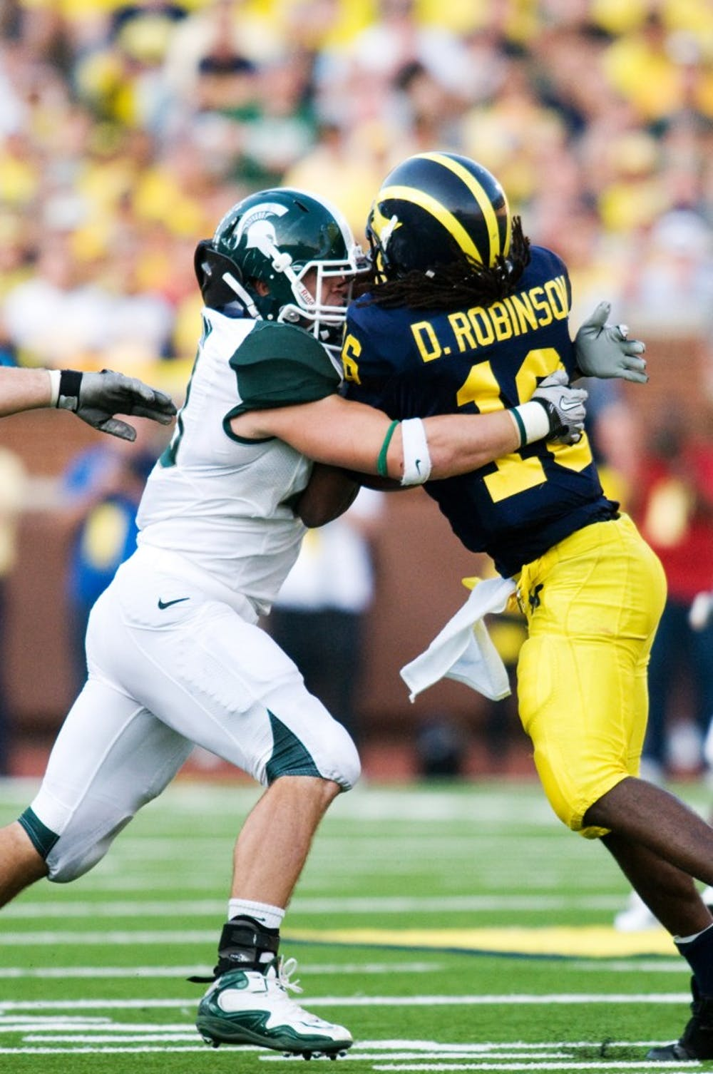 Senior linebacker Eric Gordon tackles Michigan quarterback Denard Robinson as he attempts to scramble Saturday afternoon at Michigan Stadium in Ann Arbor. Robinson had a season low of only 86 yards rushing against Spartan defense. Sam Mikalonis/The State News