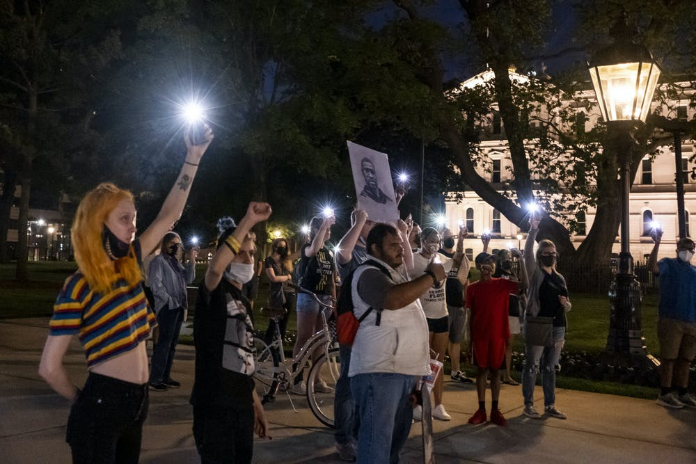 <p>Gatherers at the event for the one-year anniversary of George Floyd&#x27;s death hold up their phone flashlights and a portrait of George Floyd at Michigan&#x27;s Capitol building on May 25, 2021.</p>