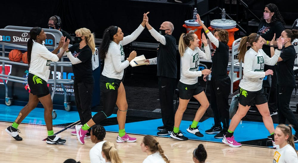 Coach Suzy Merchant, along with the rest of the coaching staff, high five the team as they prepare for their game against Iowa. The Spartans fell to the Hawkeyes, 87-72, in the semifinals of the Big Ten Tournament on Mar. 12, 2021.