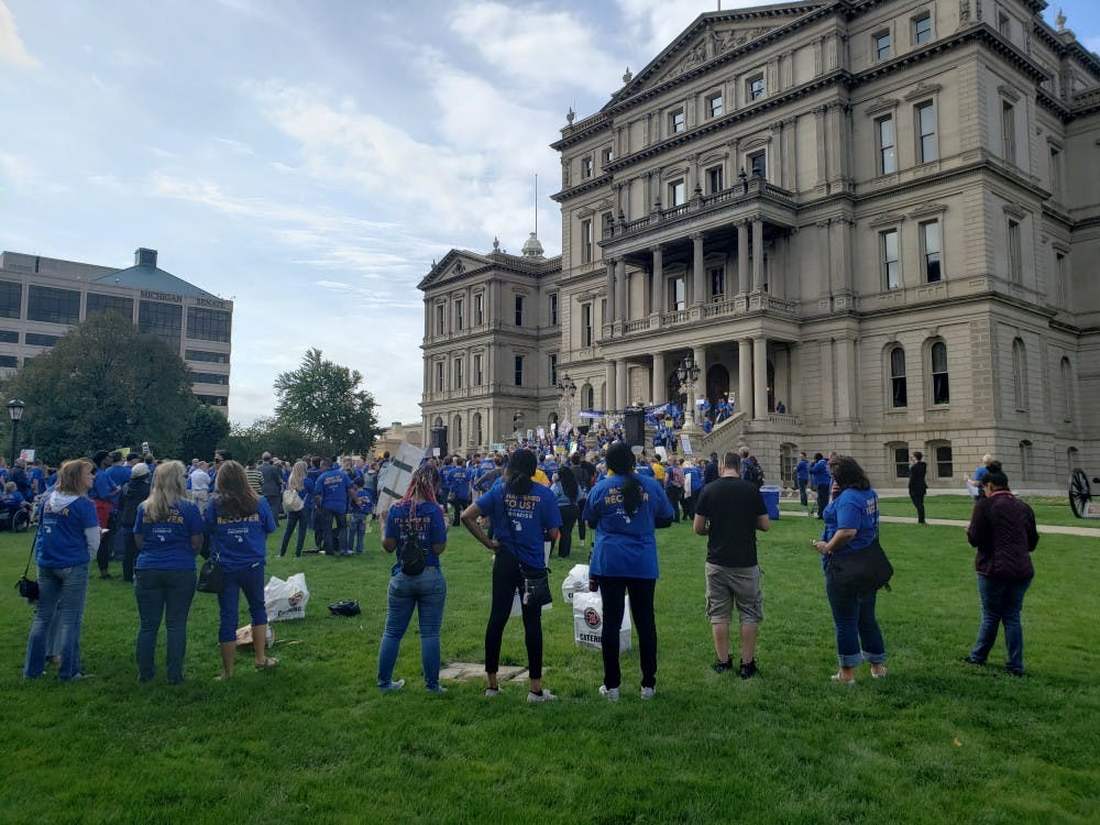 <p>Protesters rally against the new no-fault auto insurance law on Sept. 25 at Michigan&#x27;s State Capitol. </p>