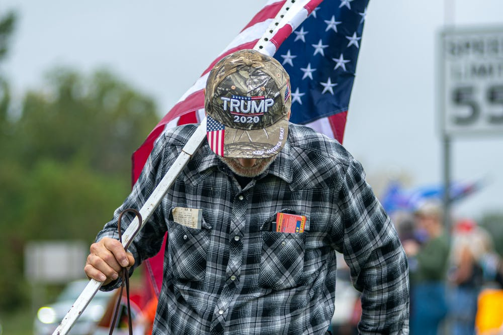 <p>A man walks with an American flag and Trump hat on Oct. 5, 2021, at the &quot;Stop the Spending&quot; protest in Howell. </p>
