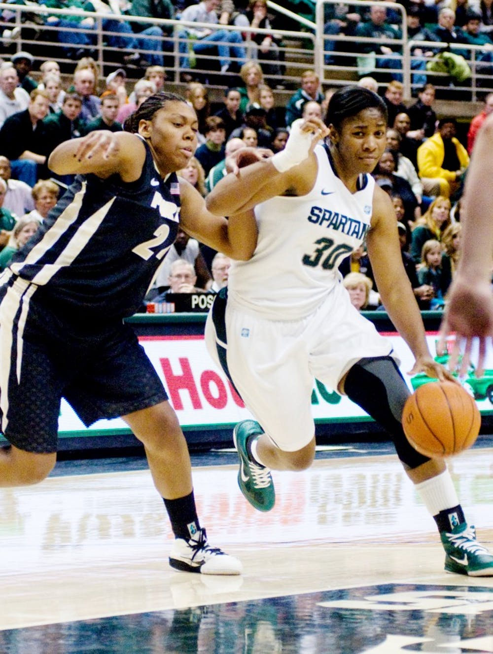 Junior forward Lykendra Johnson drives past Purdue forward Drey Mingo Sunday at Breslin Center. Johnson contributed 13 points and eight rebounds to the Spartans' 76-57 victory over the Boilermakers. Matt Radick/The State News