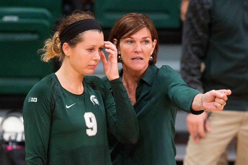 <p>Head coach Cathy George talks to senior outside hitter Taylor Galloway during a timeout during a game against LIU Brooklyn on Sept. 19, 2014, at Jenison Field House. The Spartans lost, 3-2. Julia Nagy/The State News</p>