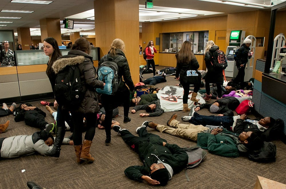 <p>Protesters lie down in the middle of the floor while other students step over them Dec. 7, 2014, during a die-in protest at the MSU Library. The group of students blocked the entrances and walk ways in the library and marched afterwards in protest of police violence against black people while other MSU students were present to study for finals week. Raymond Williams/The State News</p>