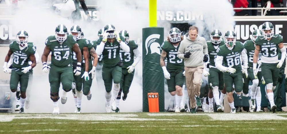 <p>The MSU football team runs out onto the field before the game begins against Ohio State on Nov. 19, 2016 at Spartan Stadium. The Spartans were defeated by the Buckeyes, 17-16.</p>
