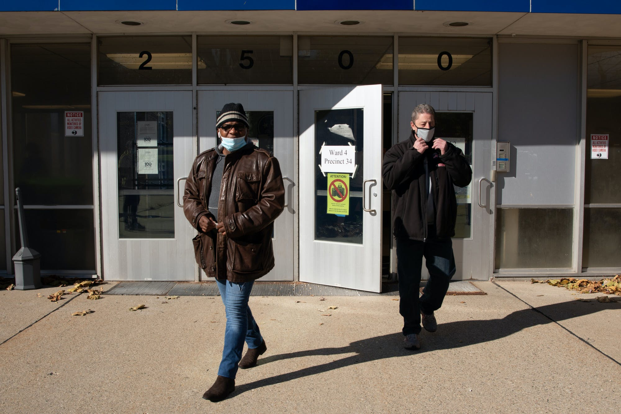 Two people walk out of a voting location.