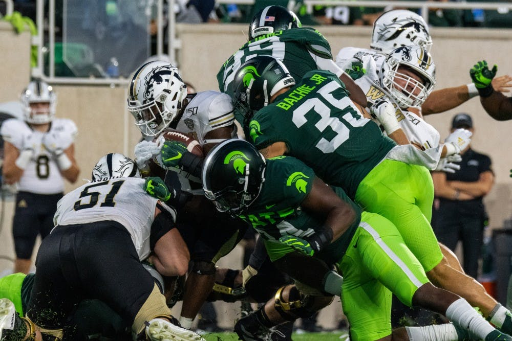 <p>Senior Linebacker Joe Bachie Jr. (35) and junior linebacker Antjuan Simmons (center) tackle a Western Michigan player. The Spartans defeated the Broncos, 51-17, at Spartan Stadium on September 7, 2019. </p>