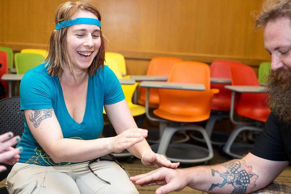<p>Saginaw, Mich., resident Leighann Zuzula , left, taps on Saginaw, Mich., Don Zuzula, right, July 2, 2014, during MSU Maker Day at the Main Library. They were both hooked up to an electronic drum set that would produce sounds upon physical contact. Master of Arts in Educational Technology students developed activities and games that integrated technology. Corey Damocles/The State News </p>
