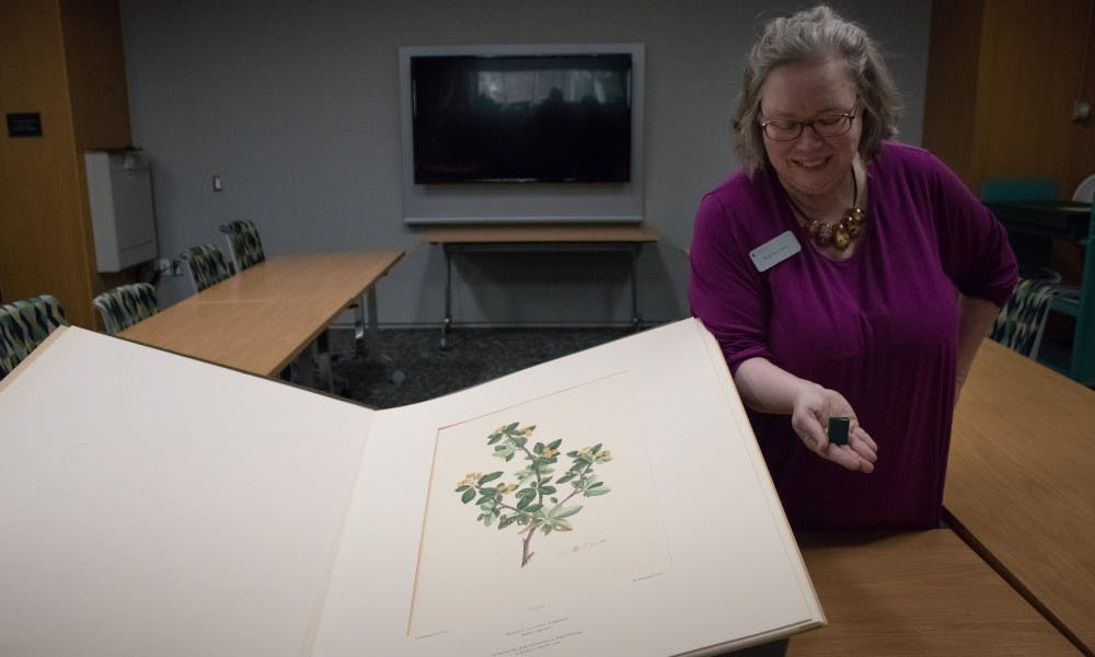 Ruth Ann Jones, the special collections education and outreach librarian, holds the library's smallest book next to the largest book at the Special Collections Seminar Room at the Main Library on Jan. 11, 2019. Every Friday throughout the semester Jones will showcase documents from the collections from various themes.