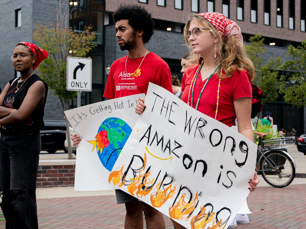 <p>Michigan State students, senior political science Kevin Hayes and junior social relations and policies Nora Kaltenbach hold signs at the &#x27;Climate 911&#x27; protest in East Lansing on Oct. 10, 2021.</p>