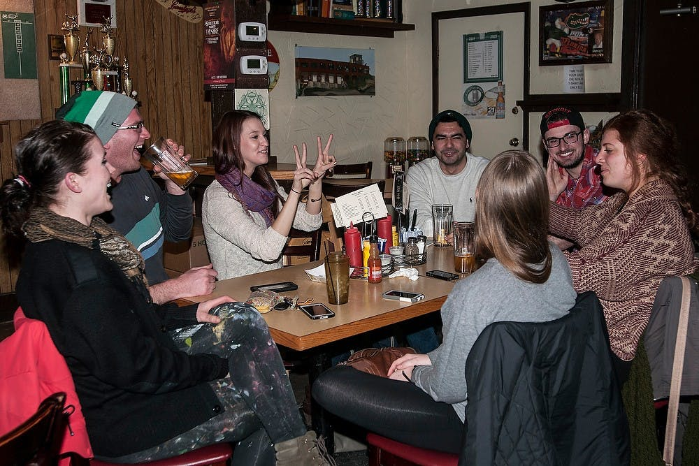 <p>Ann Arbor resident Rosemarie Royce tells her friend, alumna Natassa Christides, how to pose for a photo Feb. 24, 2015, at the Peanut Barrel, 521 E. Grand River Ave. The group was celebrating Christides' 22nd birthday over drinks. Allyson Telgenhof/The State news.</p>
