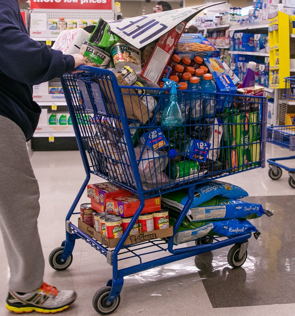 A man pushes a full cart through Meijer March 12, 2020 after MSU cancelled classes due to coronavirus.