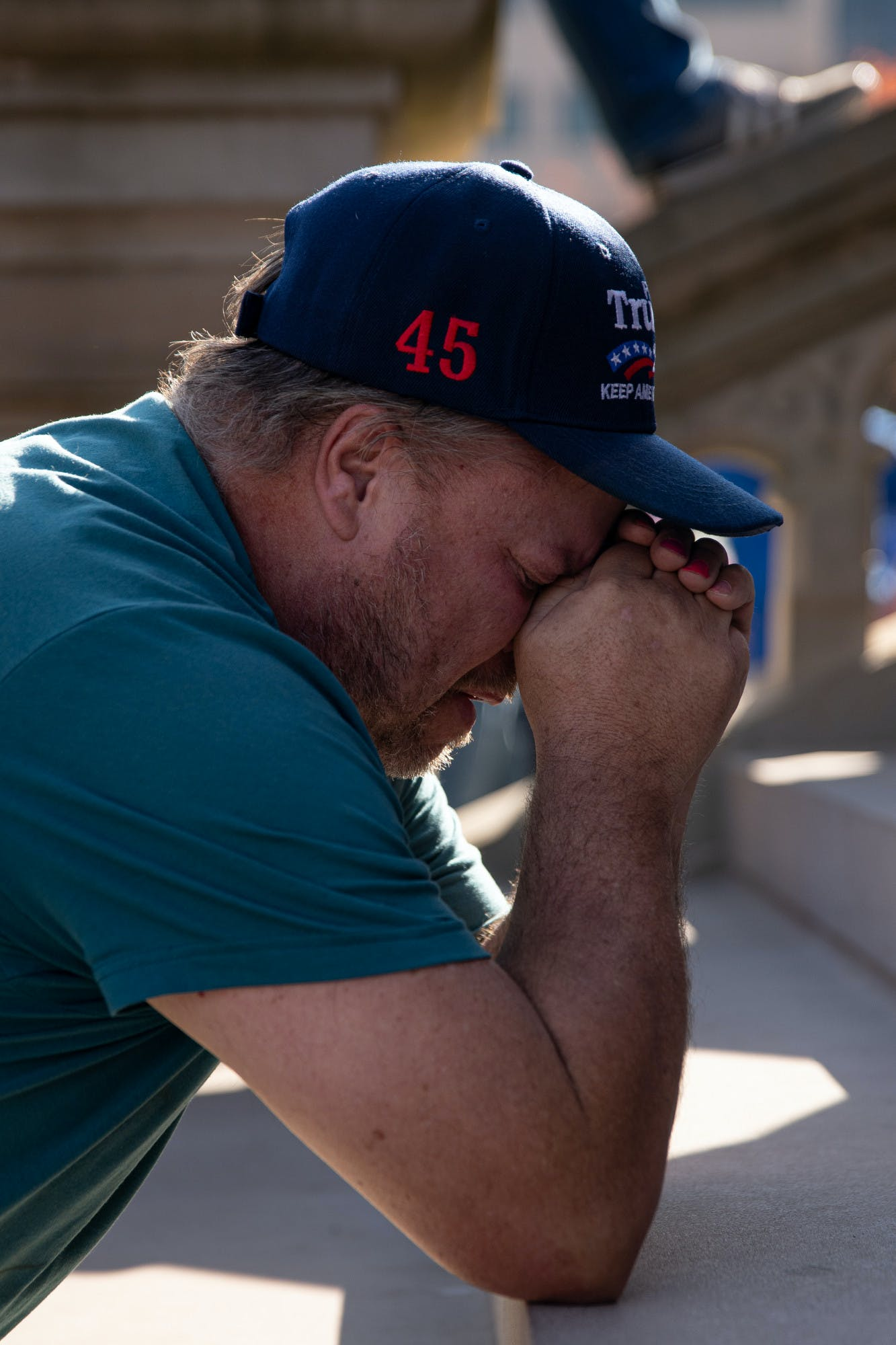 A person wearing a Trump hat prays.