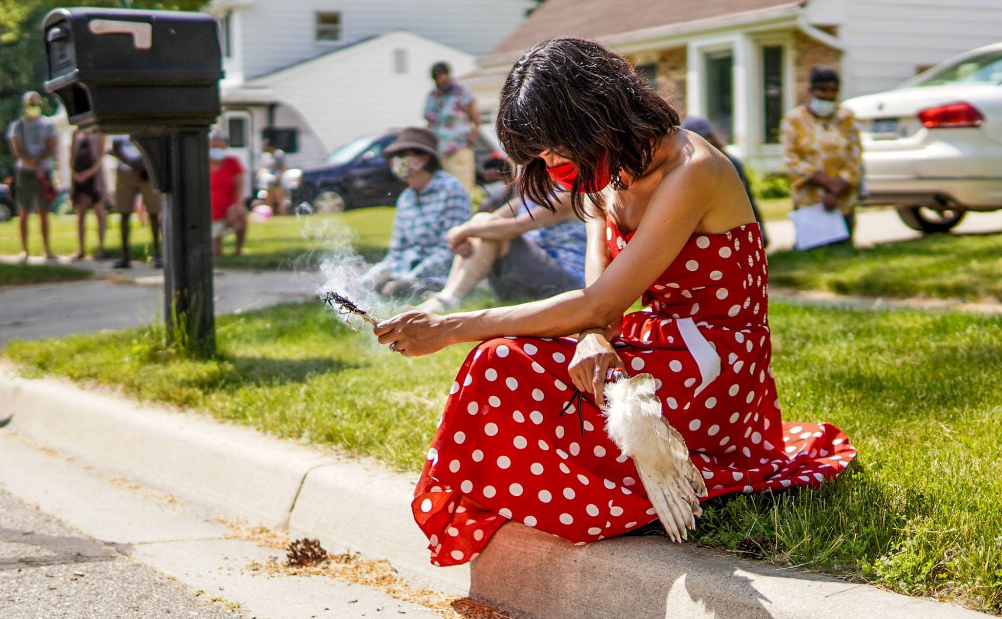 A person wearing a red polka dot dress and a face mask holds sage while sitting on a street curb.