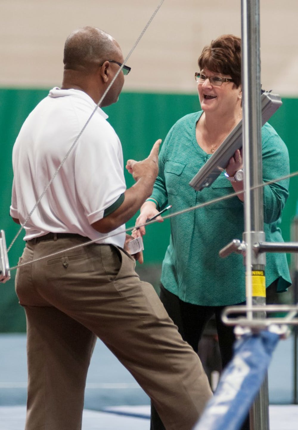 Head coach Kathie Klages and assistant coach Mo Mitchell of the MSU women's gymnastics team converse between events during a meet with Pittsburgh on Jan. 18, 2014, at Jenison Field House. Casey Hull/The State News