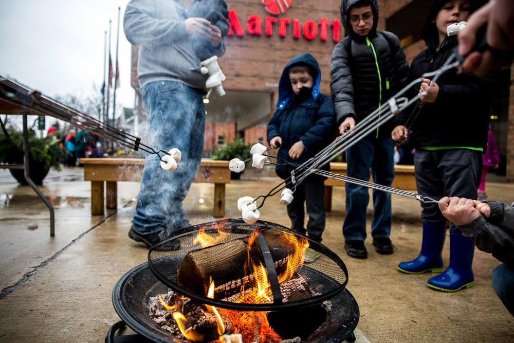 <p>People roast marshmallows during the annual Winter Glow Festival on Dec. 1, 2018 at Ann Street Plaza. The free festival featured carriage rides, music, a holiday farmers market and other seasonal activities.</p>